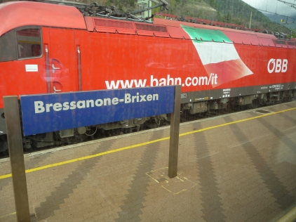 An OBB train passing through Bressanone-Brixen station all the signs have duel German and Italian names