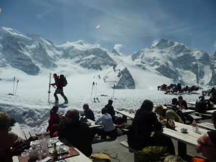 Walkers, tourists and sunbathers at the Diavolezza mountain restaurant looking towards Piz Bernina