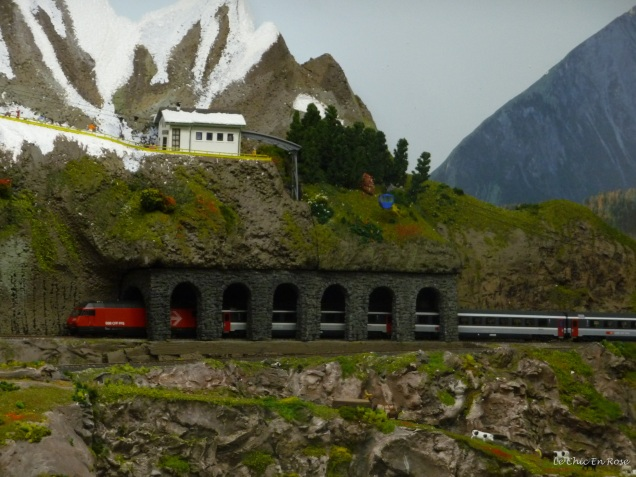 A miniature SBB Swiss rail train passes through an avalanche protection tunnel