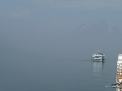 A boat appears through the mist on Lake Lucerne at Weggis