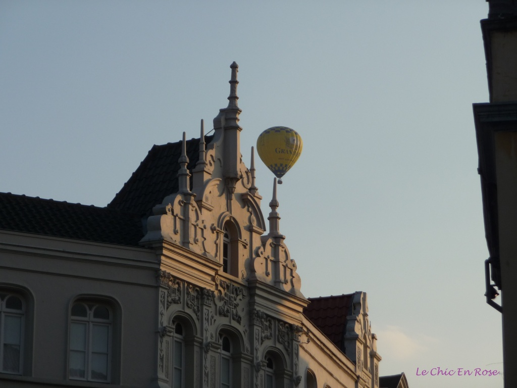 Hot air balloon flying over the old medieval town centre of Bruges at twilight